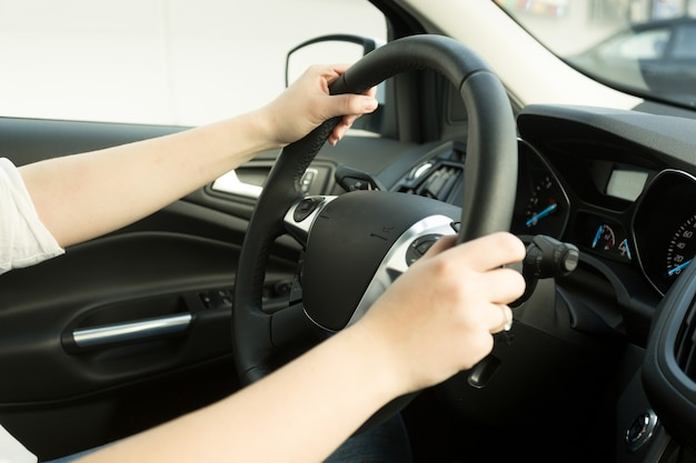 자동차를 운전하고 스티어링 휠에 손을 잡고 젊은 여자의 근접 촬영