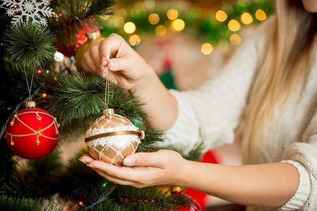 Крупным планом молодая женщина, держащая в руках золотую рождественскую безделушку