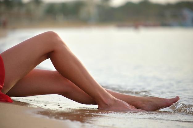 暖かい熱帯の夜を楽しんでいる海辺の海の砂浜に座っている若い女性の足のクローズアップ。