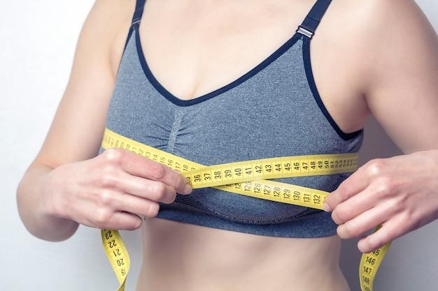 Макрофотография молодой женщины измеряет ее грудь с измеряемой Premium Фотографии
