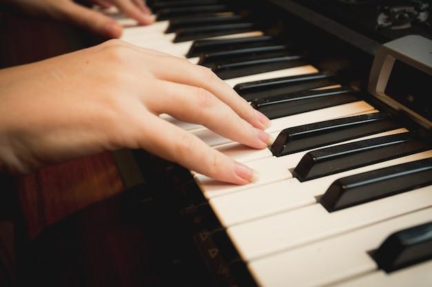 ピアノで遊ぶ若い女性のクローズアップ