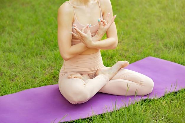 Крупным планом молодой женщины практикующих йогу утром сидя прямо