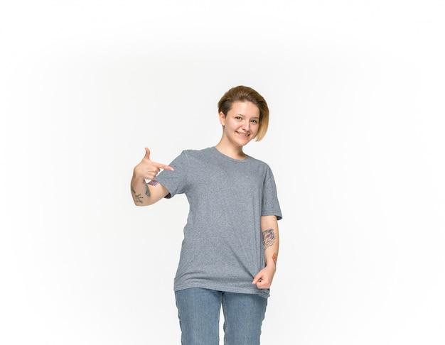 白で隔離される空の灰色のtシャツの若い女性の体のクローズアップ