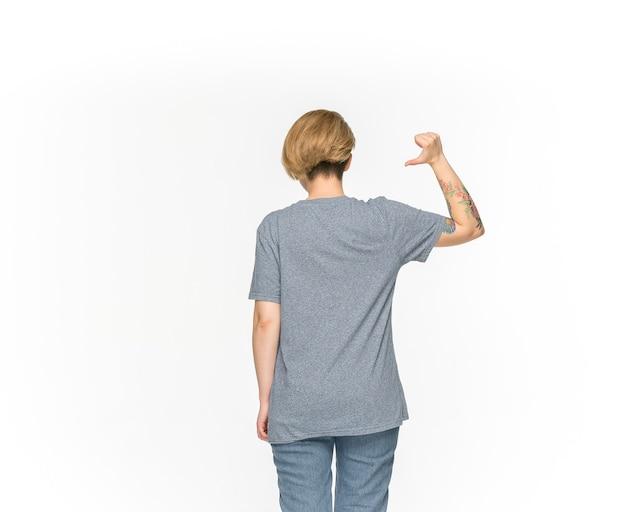 白で隔離される空の灰色のtシャツの若い女性の体のクローズアップ。