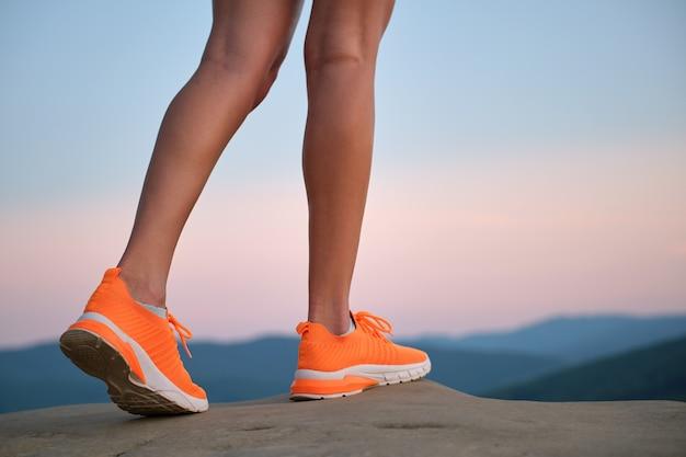 夏に山のハイキングコースを歩いている明るいオレンジ色のスニーカーの靴で若い女性のスリムな脚のクローズアップ。新鮮な空気の概念に関するアクティブな生き方と運動。