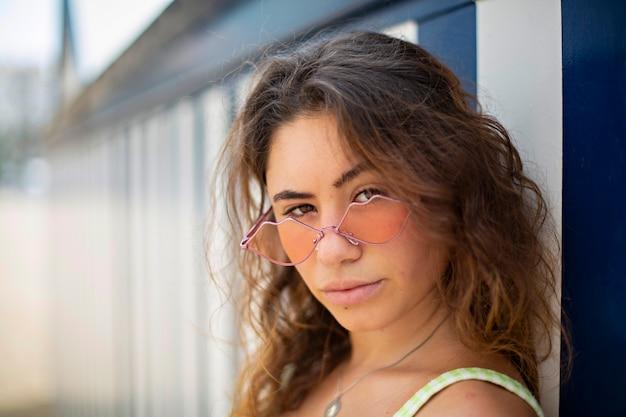 해변 오두막 앞에서 선글라스를 착용하는 젊은 여자의 근접 촬영