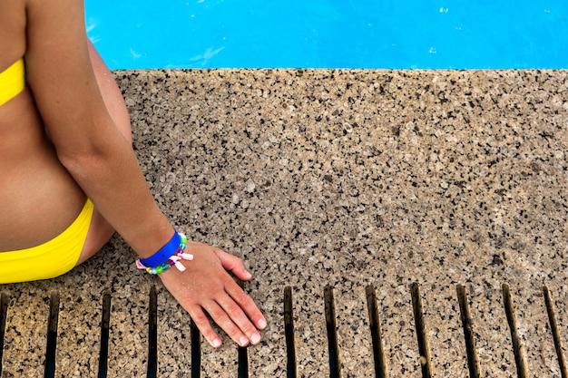 Крупный план молодой женщины нося желтый купальник бикини отдыхая около бассейна с ясным открытым морем на день лета солнечный.
