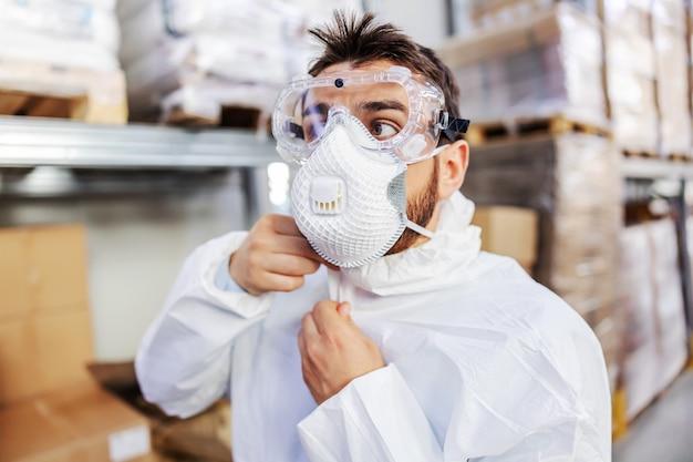 Крупным планом молодой работник в стерильной форме и защитной маске и очках на складе и застегивает форму. он готовится стерилизовать склад. концепция вспышки короны.