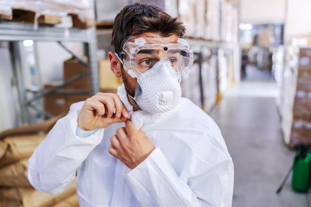 倉庫に立って制服を圧縮する際の無菌の制服と保護マスクと眼鏡の若い労働者のクローズアップ。