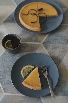 ティーセットとレモンとおいしいレモンタルトのクローズアップ。休日静物。フラットレイアフタヌーンティーブレイクテーブルトップショットレモンパイ