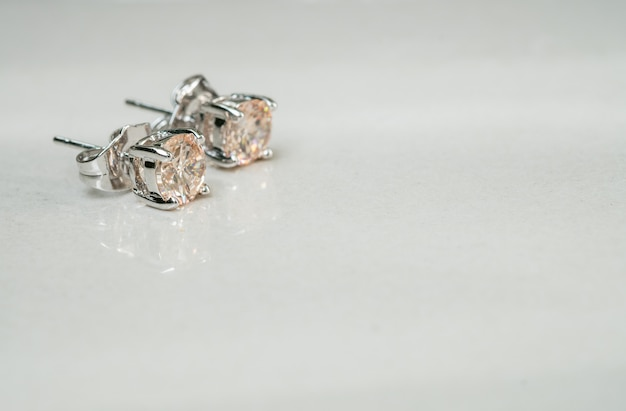 Closeup old diamond earring on blurred marble floor background