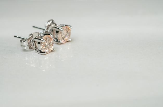 Крупным планом старые серьги с бриллиантами на размытом фоне мраморного пола