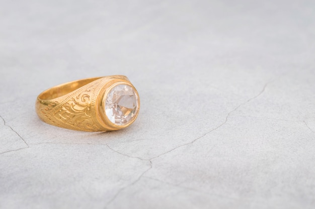 Closeup old diamond ring on blurred cement floor background