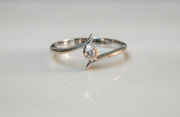 Closeup old diamond ring on blurred marble floor background
