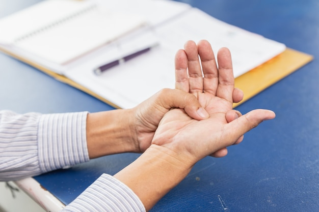 Closeup old man hand palm joint tendon muscle pain after writing work hard in office