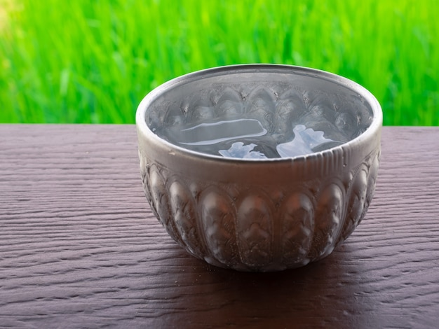 Closeup old thai style silver cup with cold water inside on wooden table with blurred natural green rice field background