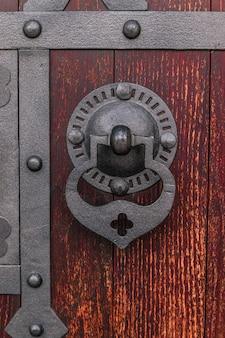 Closeup of old wooden turquoise door with aged metal door handle.