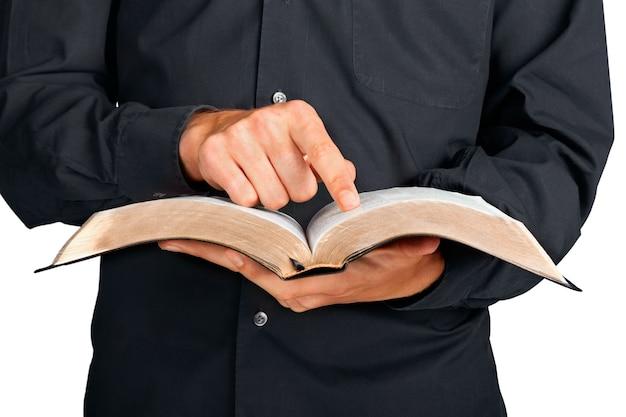 聖書と指さし指を持っている司祭のクローズアップ
