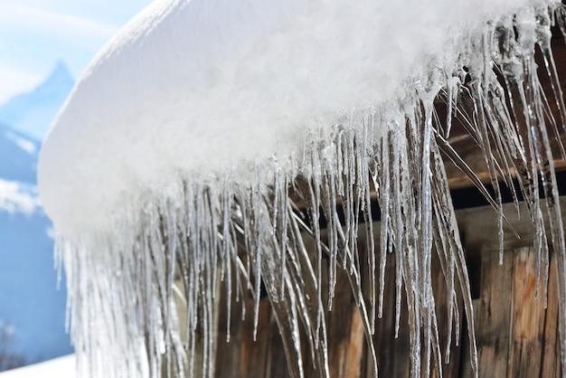 Крупным планом на крыше деревянного дома, покрытого снегом и сосульками