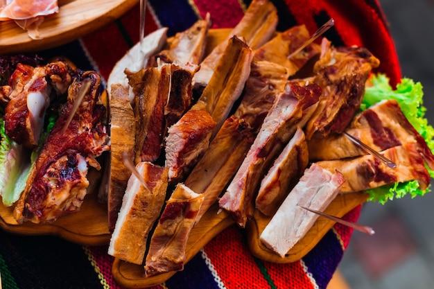 Крупным планом на деревянной тарелке с ломтиками ветчины свадебный банкет