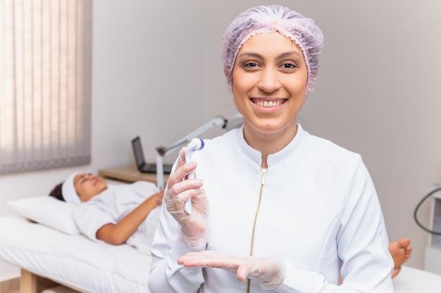 患者を背景にカメラに微笑んでマイクロニードリングを保持している美容師のクローズアップ
