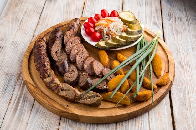 木の板にジャガイモとピクルスを添えたビーフソーセージの前菜のクローズアップ