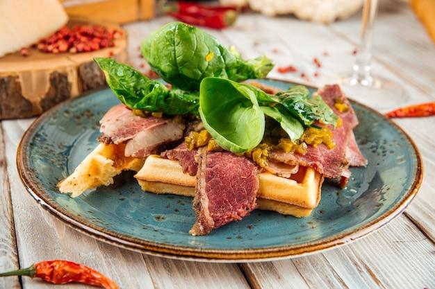 牛肉のパストラミと木製のテーブルの緑とベルギーワッフルへのクローズアップ