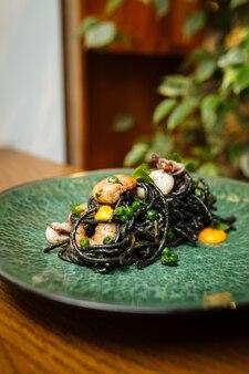 シーフードとサフランソースの黒いスパゲッティのクローズアップ