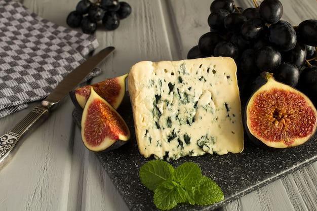 ブルーチーズと灰色の表面の果物のクローズアップ