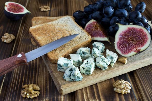 ブルーチーズ、トースト、茶色のまな板の果物のクローズアップ