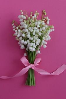 ピンクの表面の谷のユリの花束のクローズアップ。春の花のコンセプト。