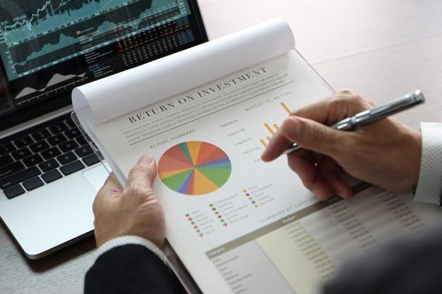 Крупный план на руках бизнесмена или аналитика, держащего финансовую отчетность с обзором рентабельности инвестиций, рентабельности инвестиций, анализ инвестиционных рисков перед портативным компьютером с графиками и соответствующей информацией