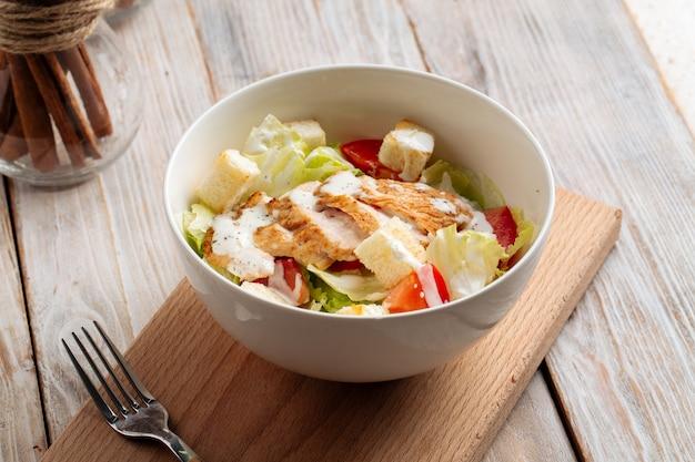 Крупным планом на салат цезарь с курицей на деревянной доске