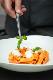 Крупным планом на руку повара готовить пенне пасты с сыром моцарелла