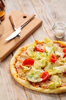 Крупным планом на куриной пицце цезарь с помидорами и салатом