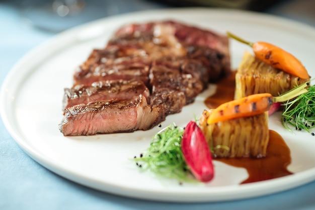 Крупным планом нарезанный стейк рибай из говядины с картофелем на белой тарелке