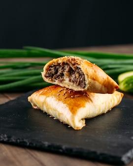 黒石のプレートに肉サムサとカットオリエンタル料理焼きパイのクローズアップ