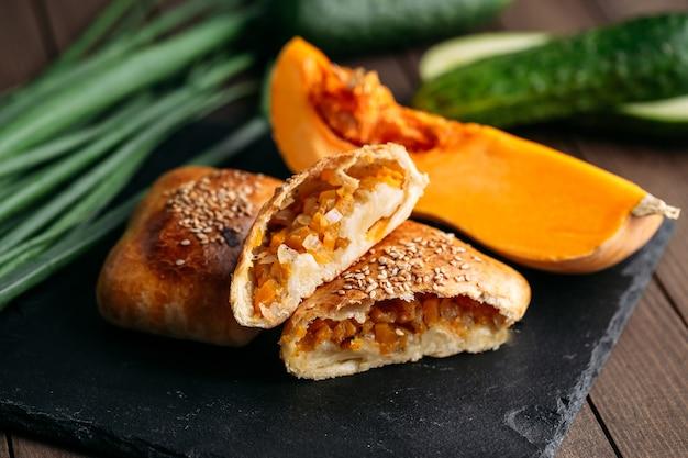 黒石のプレートにカボチャのサムサとカットオリエンタル料理焼きパイのクローズアップ