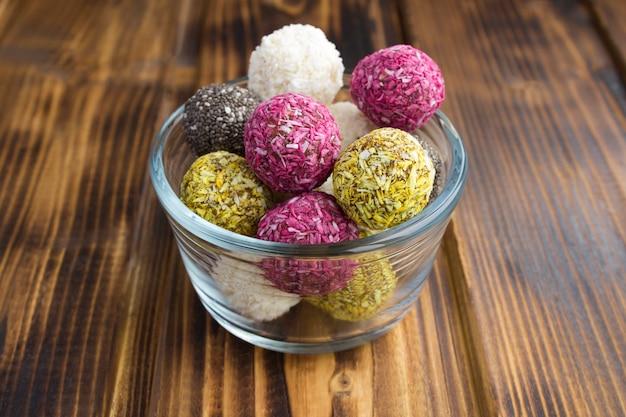 ガラスのボウルのさまざまなエネルギーボールと木製のテーブルの食材のクローズアップ
