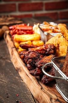 Крупным планом на жареные соленые закуски к пиву на деревянной доске с соусами