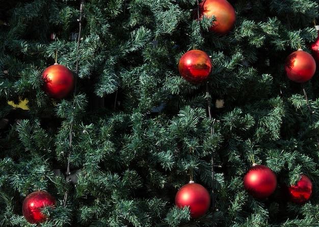 大きな赤いボールと緑のクリスマスツリーのクローズアップ冬の休日の装飾の概念
