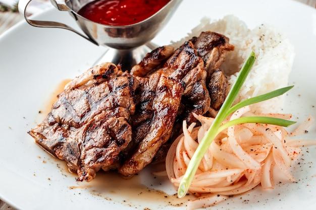 牛肉のグリルライスと木製の装飾が施されたテーブルに赤いソースのクローズアップ