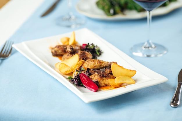 Крупным планом на курицу-гриль с картофелем на обслуживаемом столе ресторана