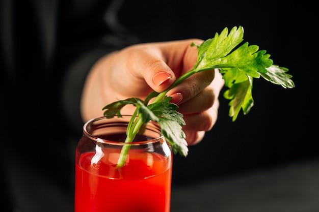 セロリの茎と血まみれのメアリーカクテルを作る手でクローズアップ