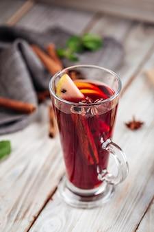 Крупным планом на горячий пряный напиток глинтвейн с яблоком и корицей