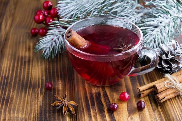 Крупным планом на горячий чай с клюквой и специями в стеклянной чашке на деревянном фоне