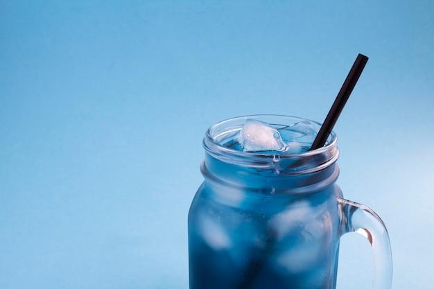 Крупным планом на холодном голубом цветочном чае в стекле на синем