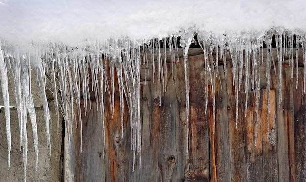 Крупным планом сосульки, образующиеся на деревянной стене шале