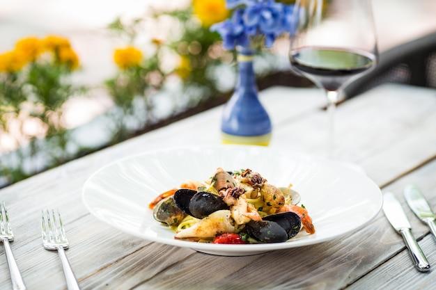 Крупным планом на итальянской пасте из морепродуктов на деревянном столе