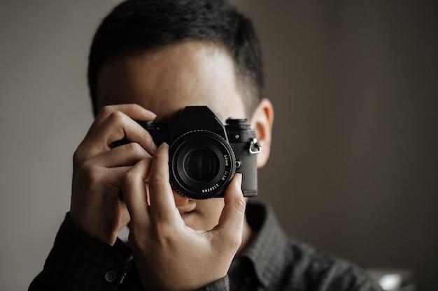 ペンタックスフィルムカメラで写真を撮る男のクローズアップ